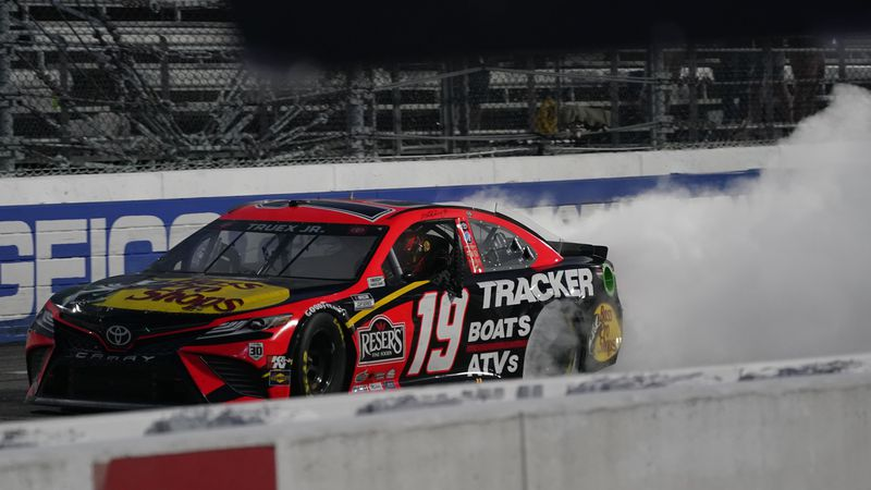 Martin Truex Jr. (19) does a burnout as he celebrates after winning a NASCAR Cup Series auto...
