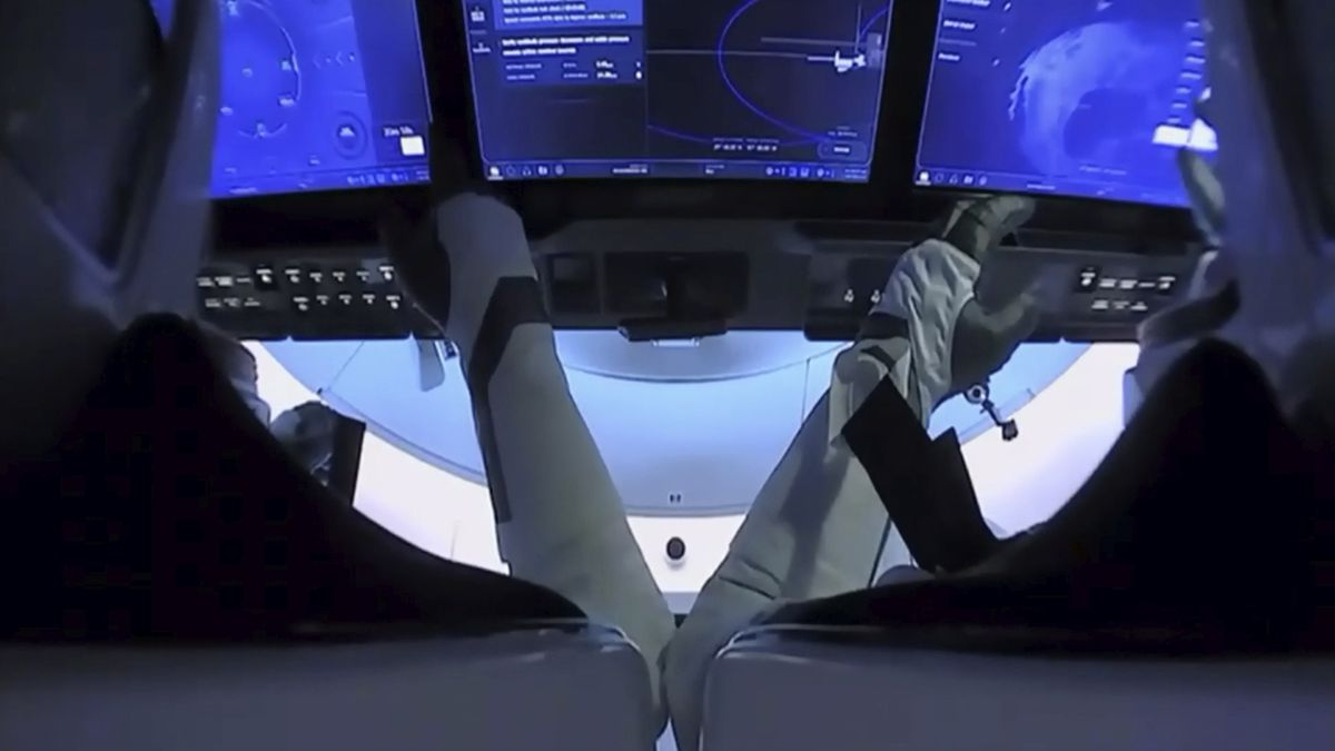 In this image from video made available by NASA, astronauts Doug Hurley, left, and Bob Behnken prepare for undocking from the International Space Station, aboard the SpaceX Crew Dragon capsule on Saturday, Aug. 1, 2020.