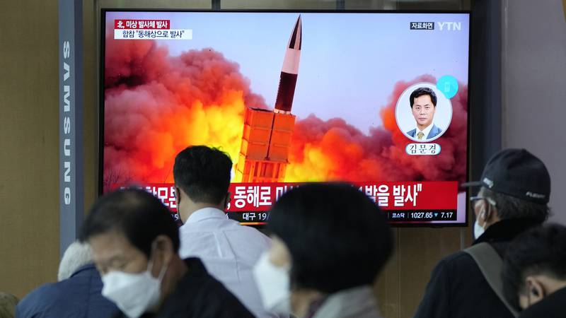 People watch a TV showing a file image of a North Korean missile launch during a news program...