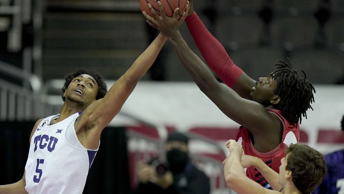 Liberty's Micaiah Abii, right, and TCU's Chuck O'Bannon Jr. (5) battle for a rebound during the...