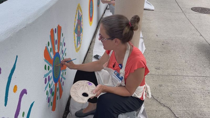 Carilion employees paint a mural outside of the hospital.