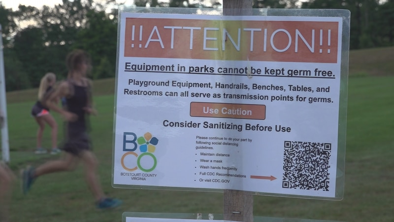 Runners with Lord Botetourt High's cross country team pass a health warning sign.
