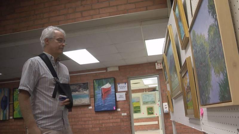 Judge John Henry Rice studies work at the Bath County Art Show.