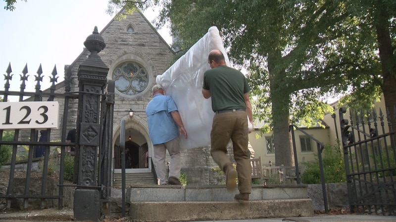 Volunteers carry in a part of the new pipe organ.