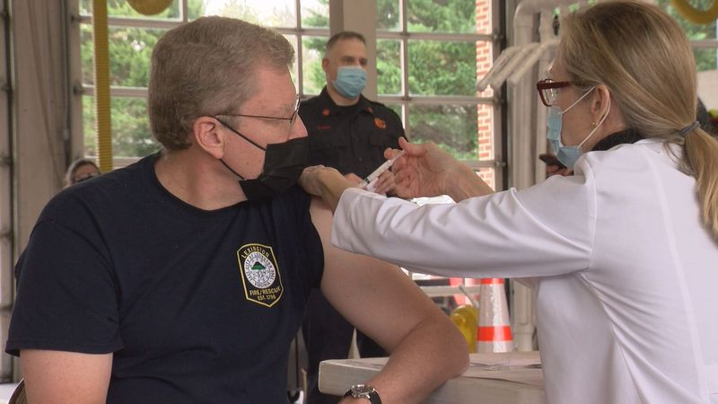 Lexington EMS volunteer James Squires receives the Moderna COVID vaccine at the firehouse in...