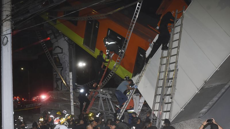 Mexico City fire fighters and rescue personnel work to recover victims from a subway car that...