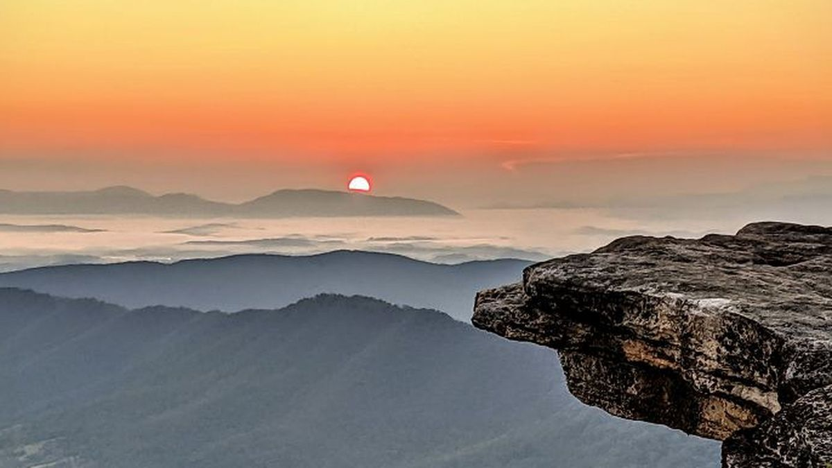A view of the sunrise at McAfee Knob with hazy skies in the distance.