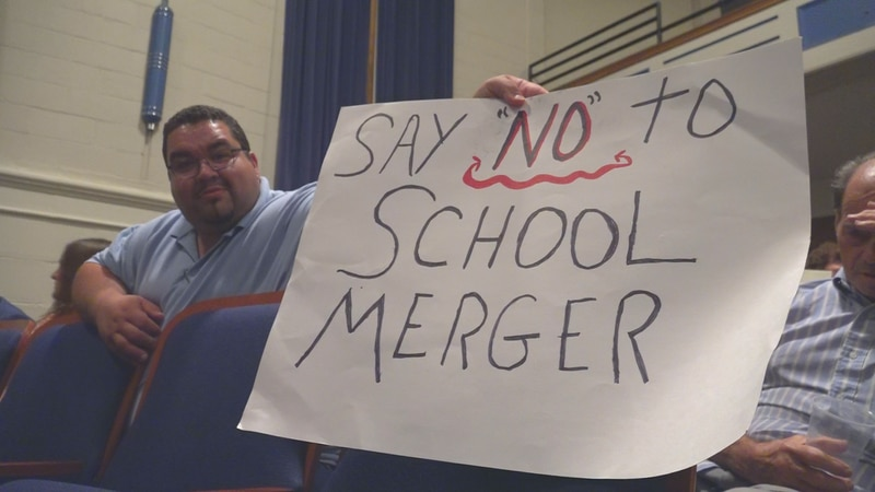 Most people who attended Thursday's meeting opposed the merger, with some waving signs, and one...