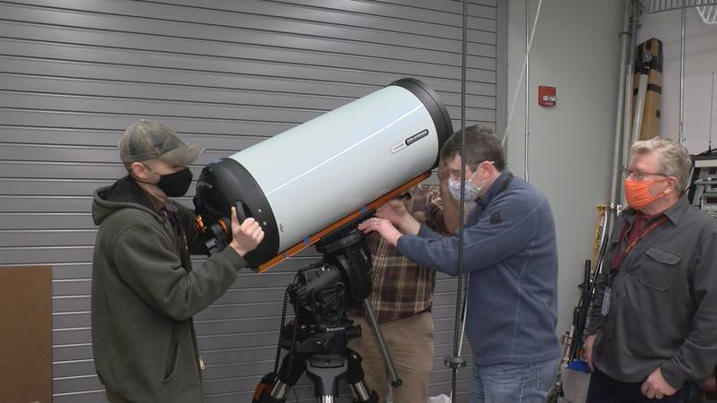 Team members carefully put their new telescope on its pedestal in The Hume Center.