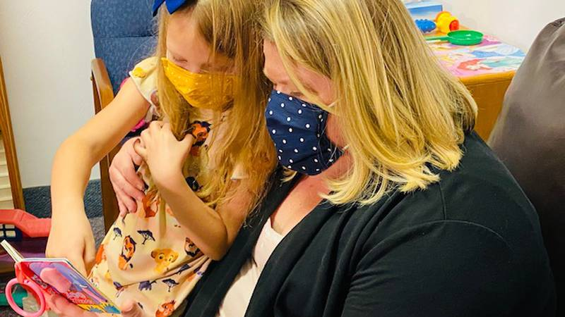 Kristina Hawse reads with one of her new adopted daughters