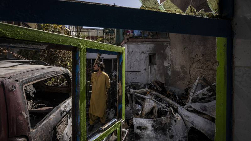 An Afghan inspects the damage at the Ahmadi family house in Kabul, Afghanistan, Monday, Sept....