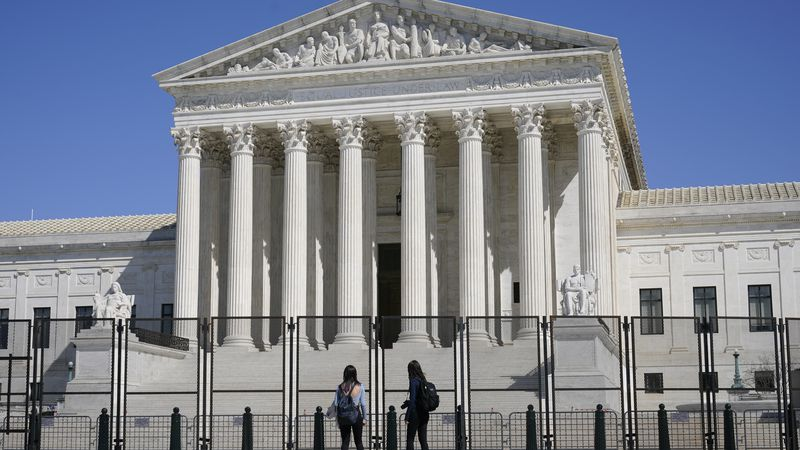 FILE - In this March 21, 2021, file photo people view the Supreme Court building from behind...