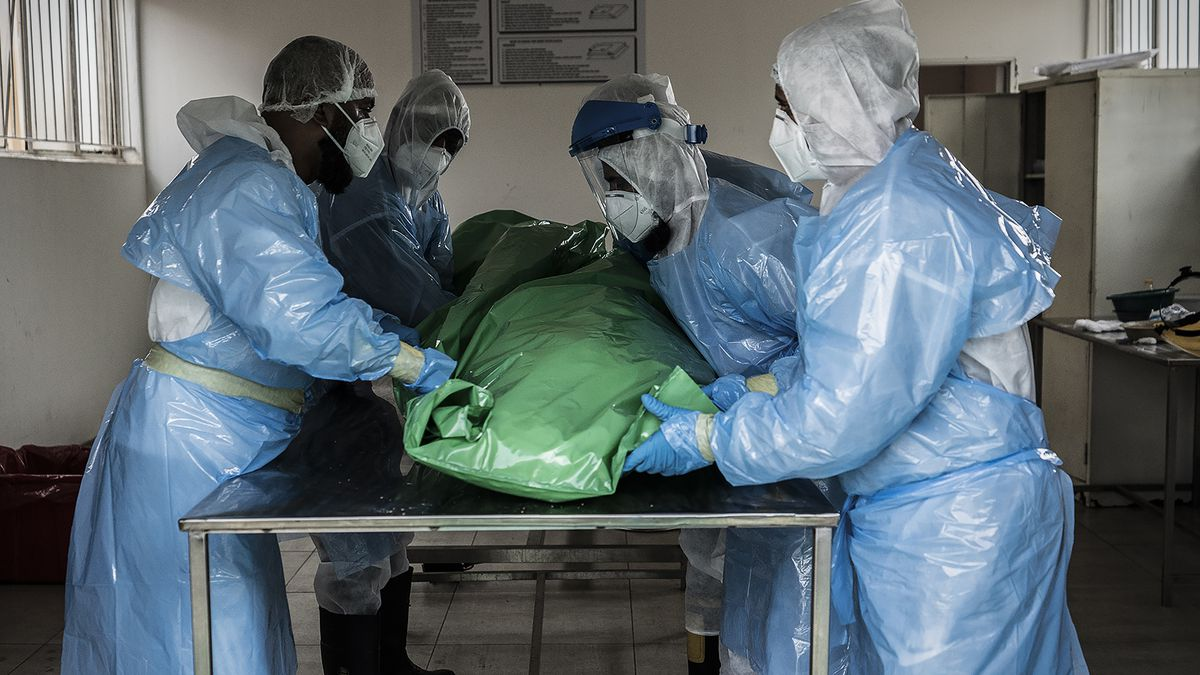 Members of the Saaberie Chishty Burial Society prepare the body of a person who died from...