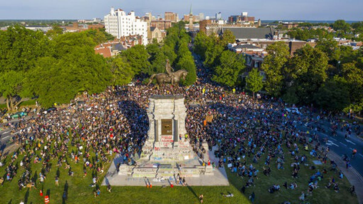 """In this photo taken with a drone, a large group of protesters gather around the statue of Confederate General Robert E. Lee on Monument Avenue near downtown Tuesday, June 2, 2020, in Richmond, Va. The crowd protesting police brutality chanted """"Tear it down."""" (AP Photo/Steve Helber)"""