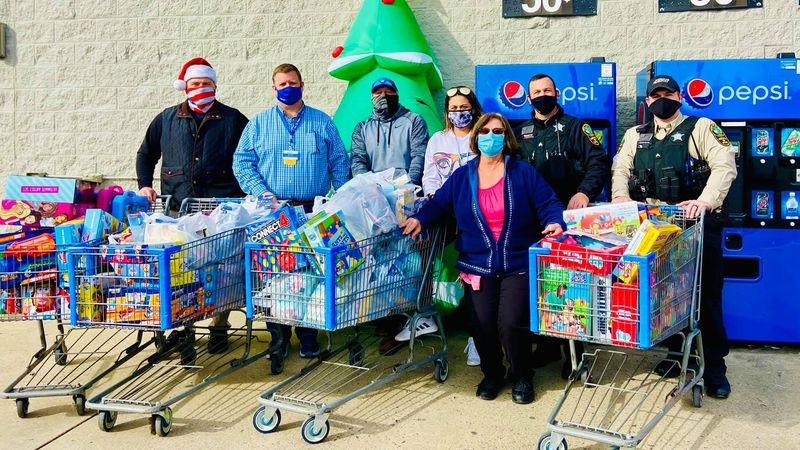Rockbridge County Sheriff's Deputies and other volunteers pose with the toys they bought at...