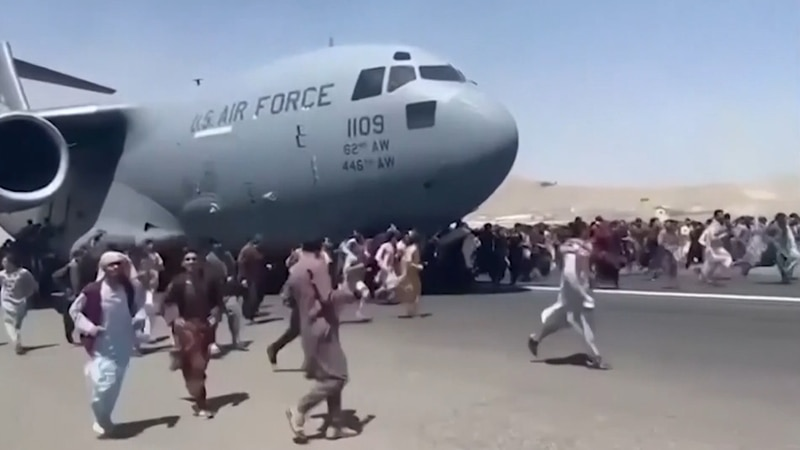 Afghan civilians desperate to leave the country try climbing abroad military transport in Kabul.