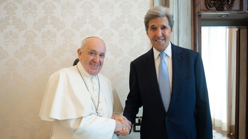 Pope Francis and John Kerry, right, shake hands as they pose for a photo at the Vatican,...