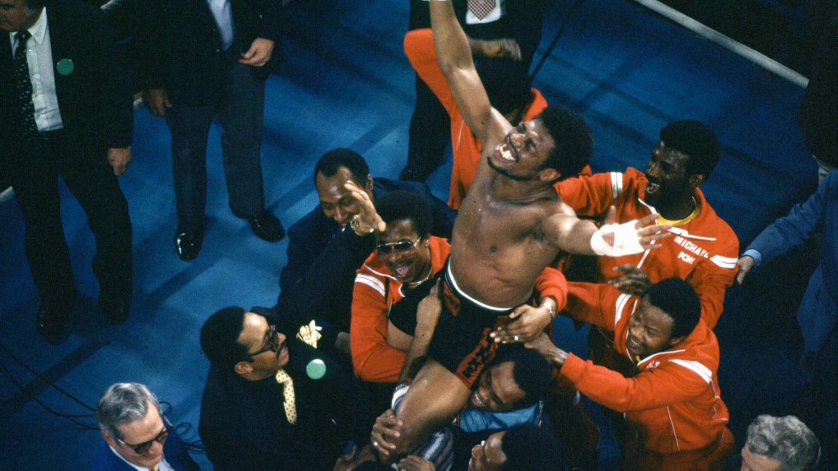FILE - In this Feb. 15, 1978, file photo, Leon Spinks celebrates as his entourage holds him...