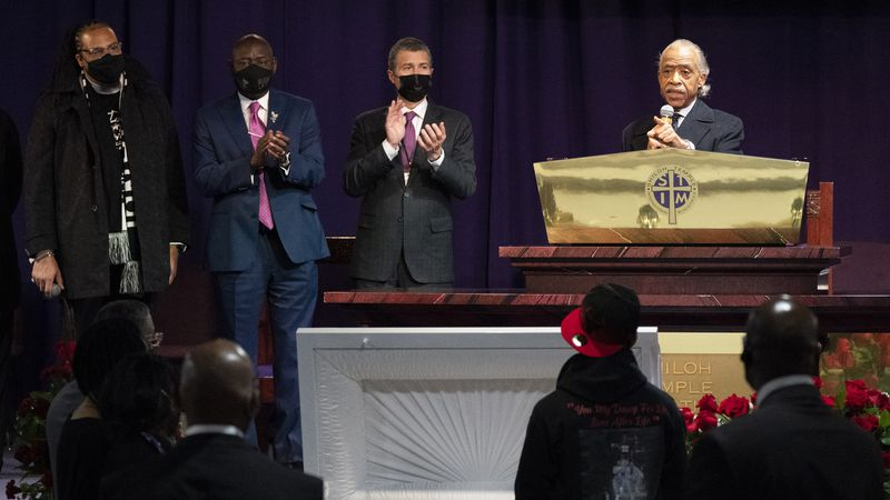 The Rev. Al Sharpton, right, speaks over the casket of Daunte Wright, alongside attorneys...