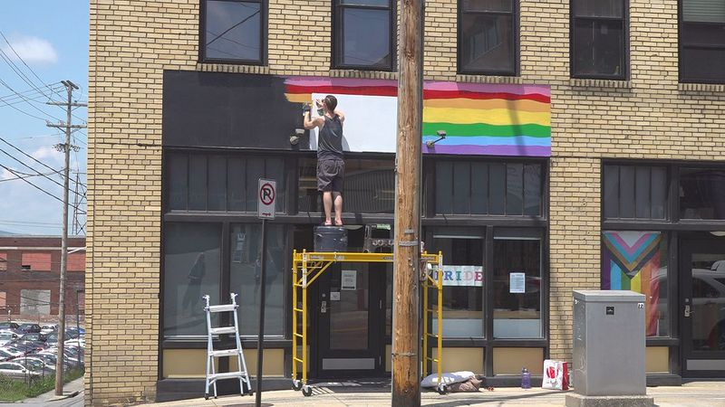 A local artist is painting a mural on the Roanoke Diversity Center building.