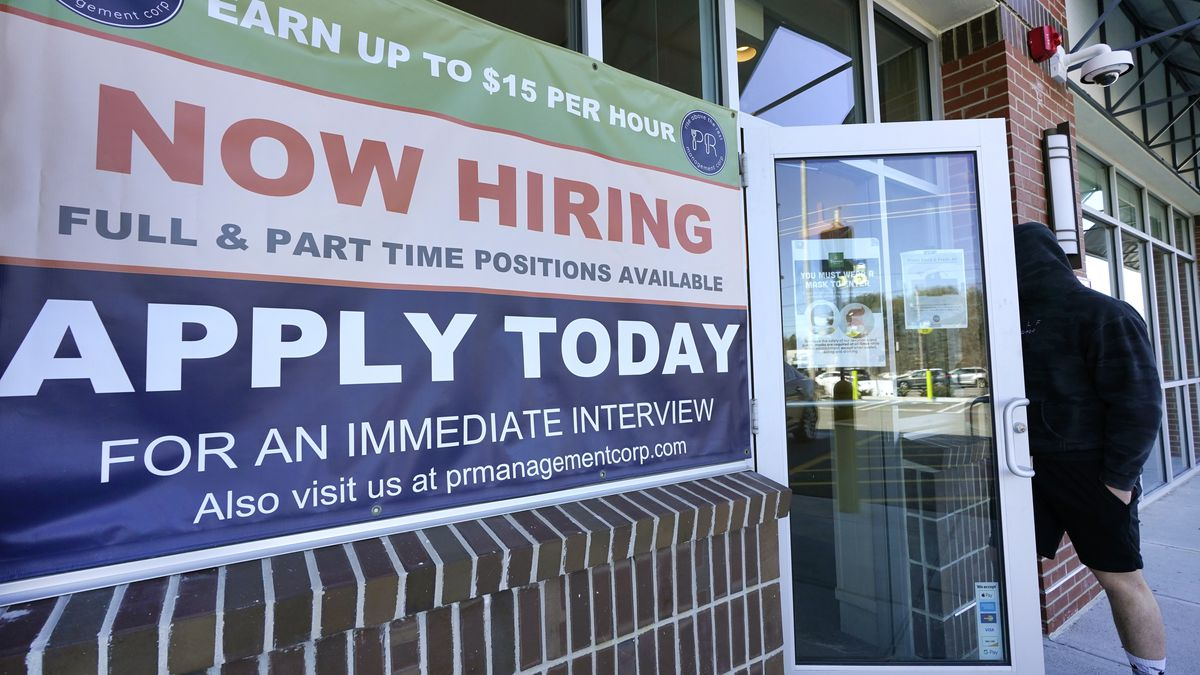 """A man walks into a restaurant displaying a """"Now Hiring"""" sign, Thursday, March 4, 2021, in..."""