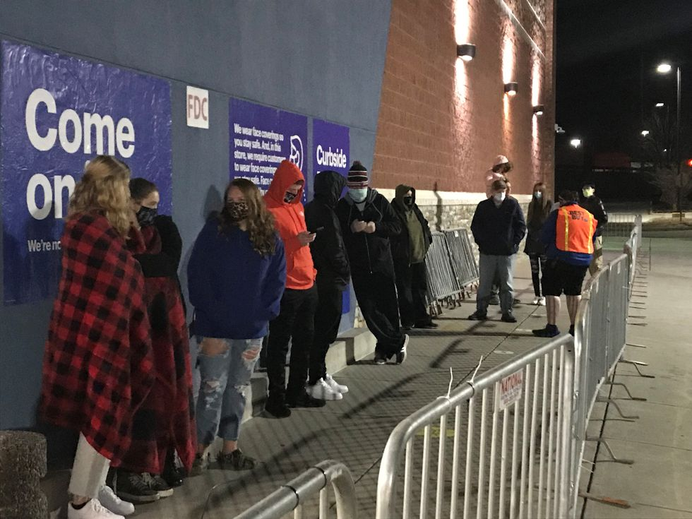 A dozen or so people stand bundled up in the cold to be the first inside Best Buy in...