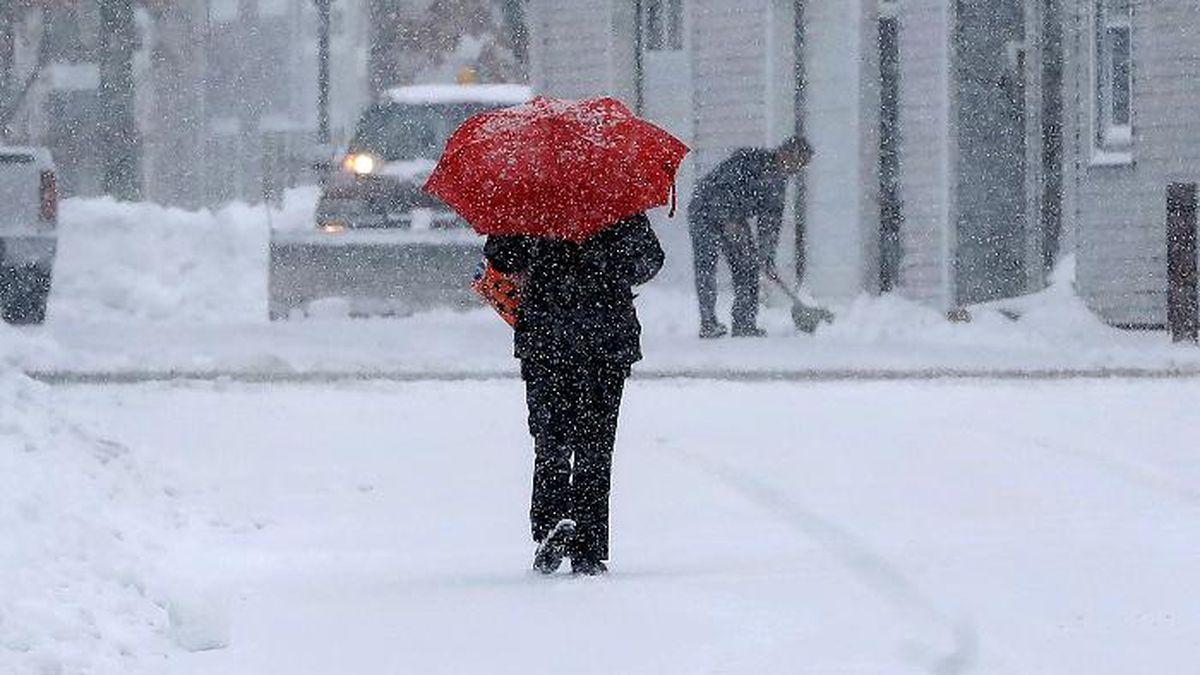 A pedestrian uses an umbrella while making their way down a snow-covered street, Tuesday, Dec. 3, 2019, in Norwood, Mass. (AP Photo/Steven Senne) (Source: Steven Senne)