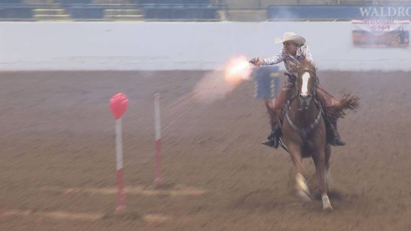 A competitor fires at a balloon at the Cowboy Mounted Shooting Championships.