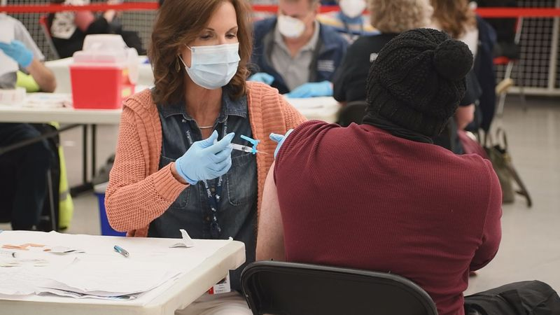 A patient receives her shot at a COVID vaccine clinic.