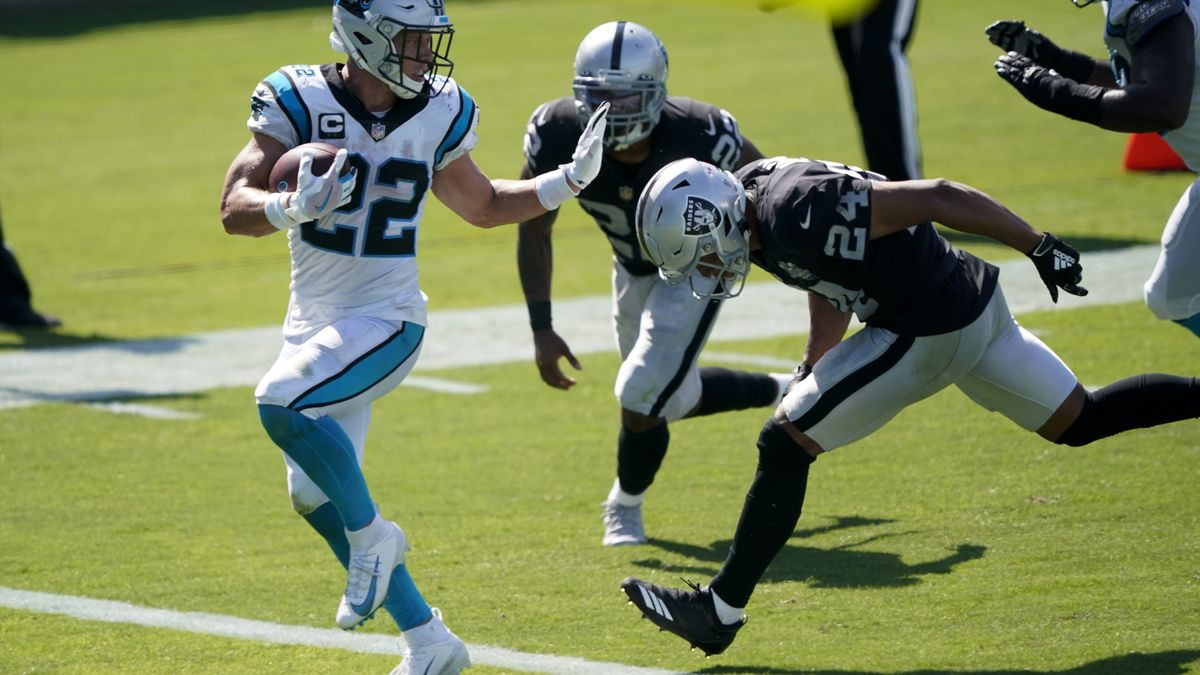 Carolina Panthers running back Christian McCaffrey scores ahead of Las Vegas Raiders safety Johnathan Abram during the second half of an NFL football game Sunday, Sept. 13, 2020, in Charlotte, N.C. (AP Photo/Brian Blanco)