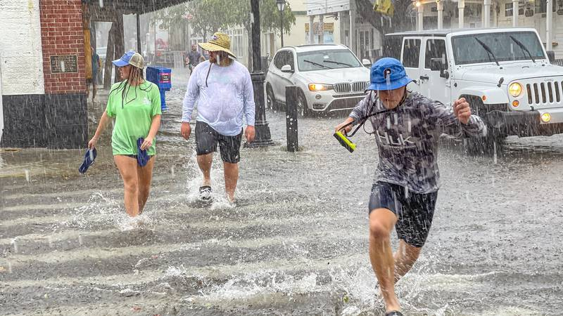 Pedestrians dash across the intersection of Greene and Duval streets as heavy winds and rain...