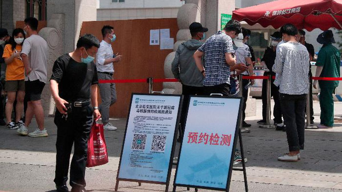 People wearing protective face masks to help curb the spread of the new coronavirus gather outside a hospital to seek information about getting the nucleic acid test in Beijing, Monday, June 15, 2020. Beijing has reinstated measures to control the spread of the coronavirus amid a growing outbreak. (AP Photo/Andy Wong)
