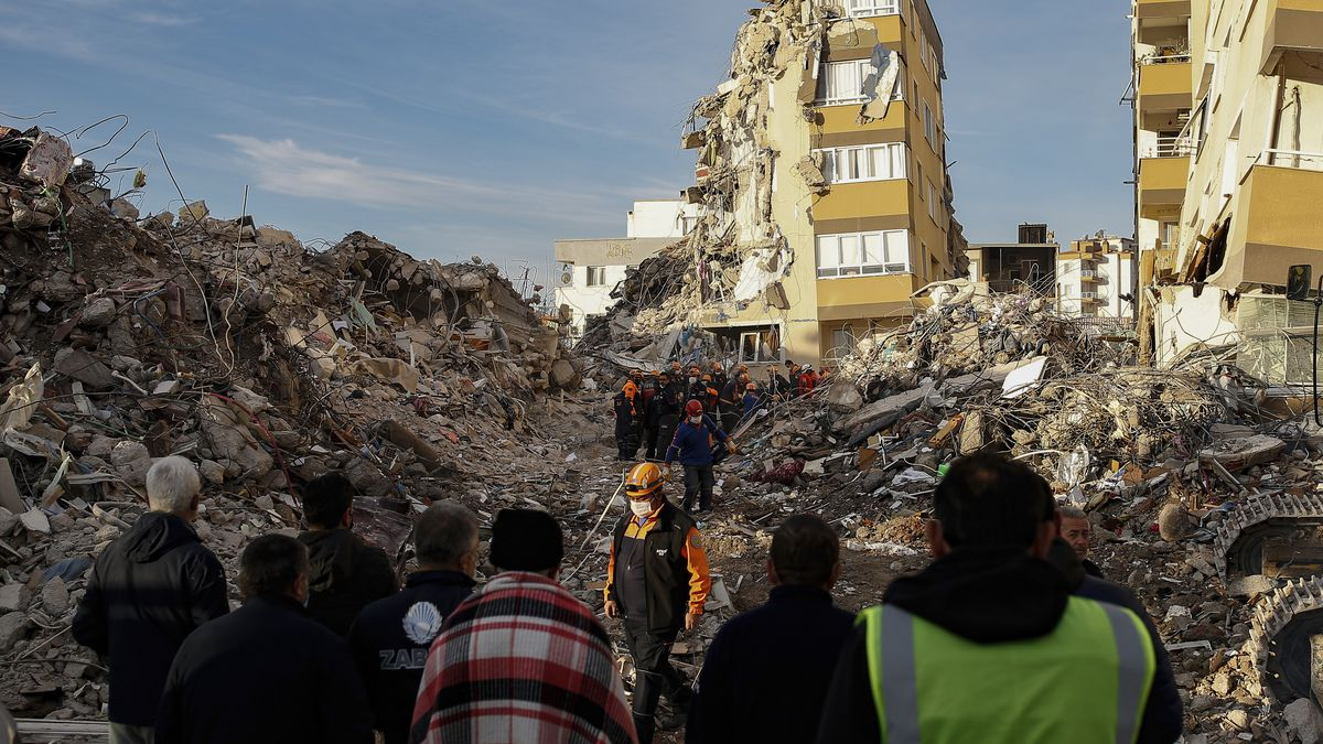 Local residents watch as members of rescue services work at collapsed buildings destroyed in...