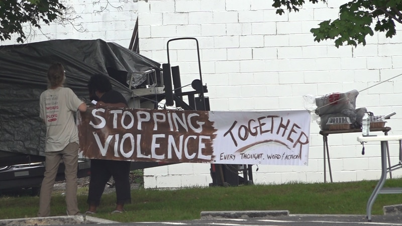"""Community members raise a banner ahead of the """"United Against Gun Violence"""" event on Saturday..."""