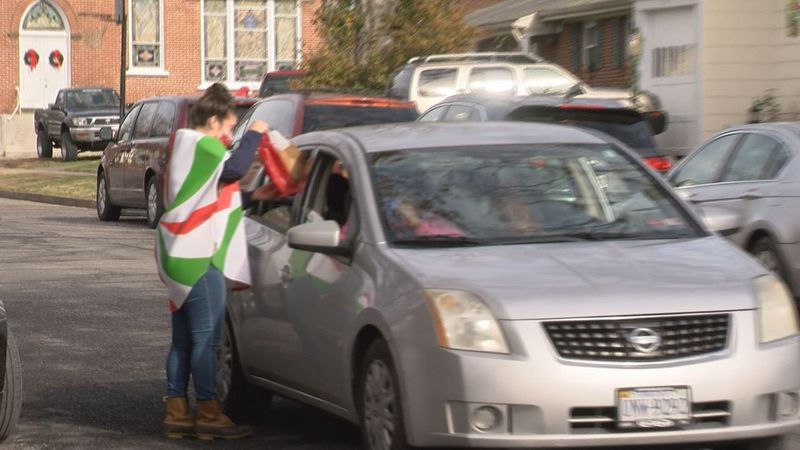 A Parry McCluer Middle School teacher passes a goodie bag to a student's family at a drive...