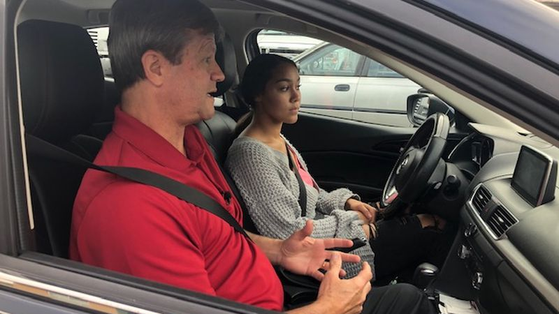 Instructor Jim Stepp gives some quick instructions to student Macy Thompson before her driving...
