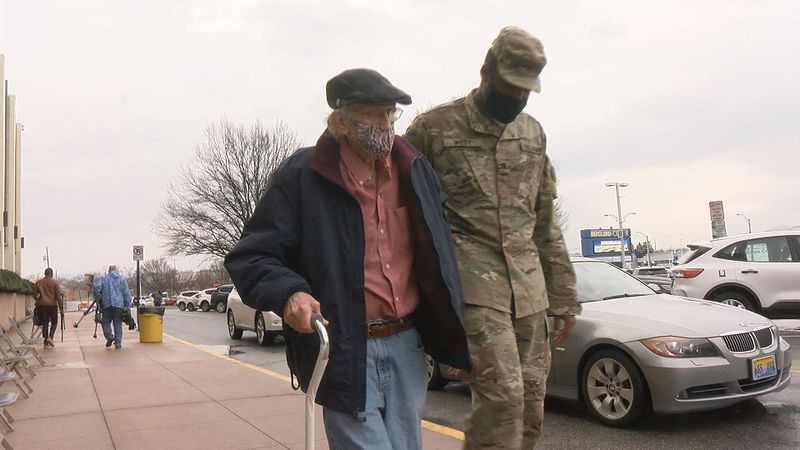 Virginia National Guard members help walk folks into the Berglund Center to get their COVID-19...