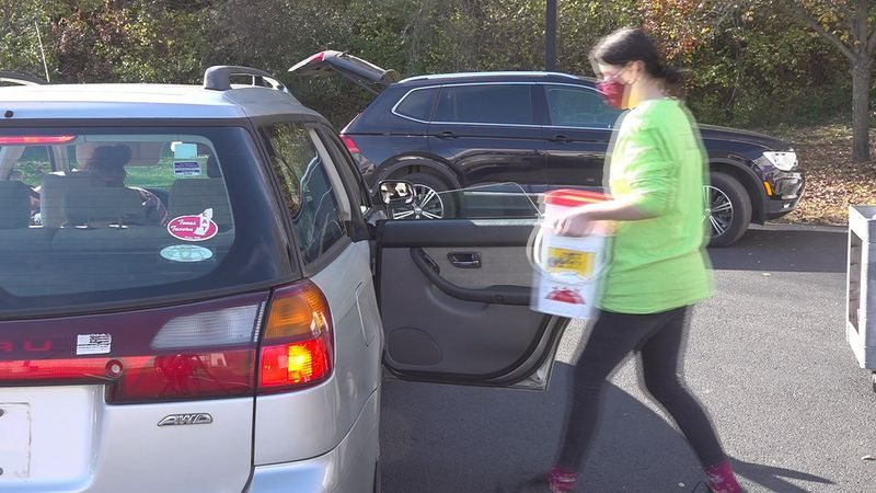 RVSPCA employees hand out free pet food at Sunday's Dot Drive-Thru