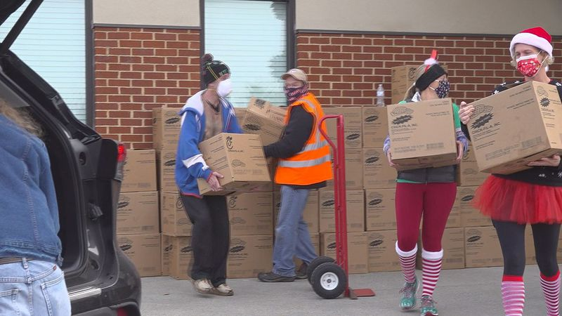 Church volunteers load their cars up with Christmas Food Boxes for families in need.