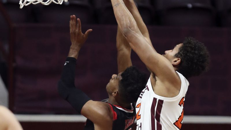 VMI's Greg Parham (5) has his shot blocked by Virginia Tech's Keve Aluma (22) during the first...