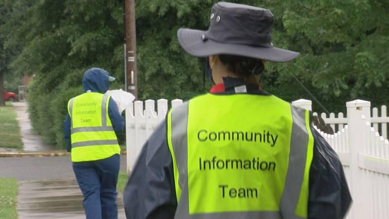 Members of a Community Information Team walk down a street in Buena Vista, Va.