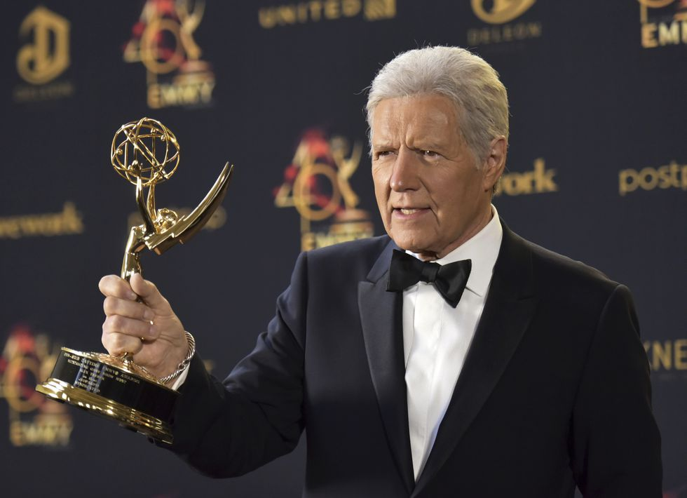 Alex Trebek poses in the press room with the award for outstanding game show host for...