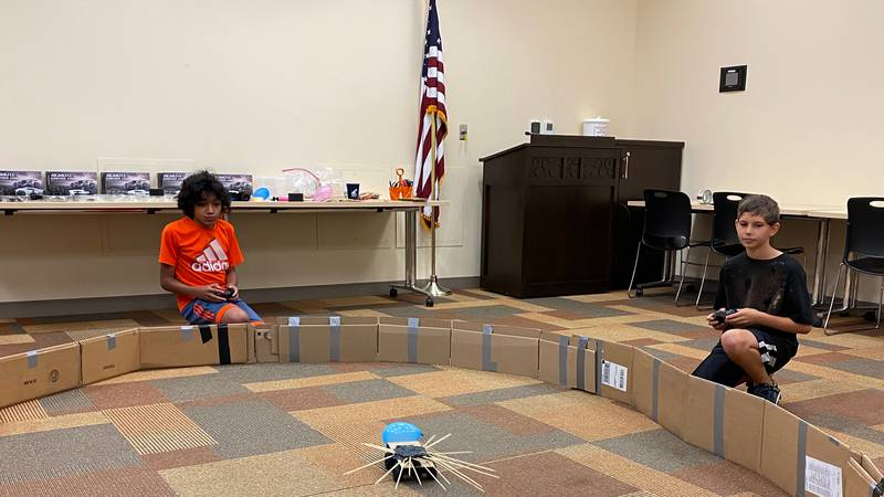 Two R-C cars decorated with skewers, tape, and balloons face off to defeat their opponent.