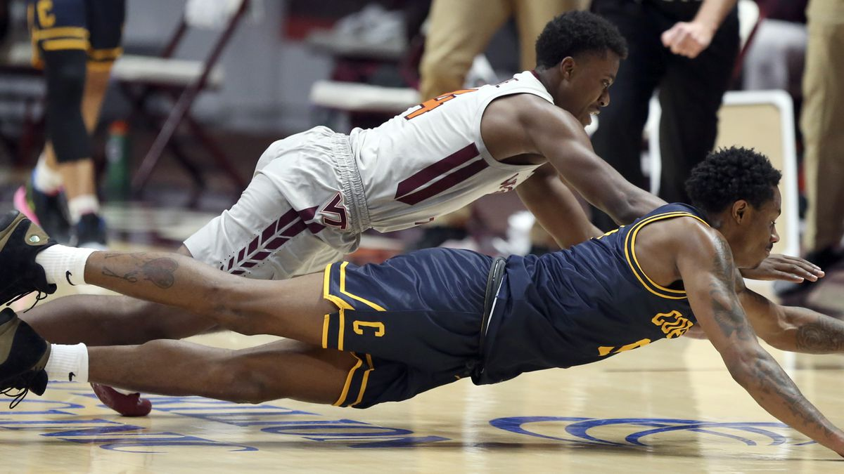 Virginia Tech's Nahiem Alleyne, top, and Coppin State's Koby Thomas dive for a loose ball...
