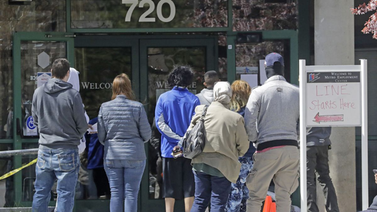 People line up outside the Utah Department of Workforce Services on Monday, April 13, 2020, in Salt Lake City. (AP Photo/Rick Bowmer)