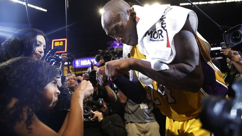 Los Angeles Lakers' Kobe Bryant, right, fist-bumps his daughter Gianna after the last NBA...