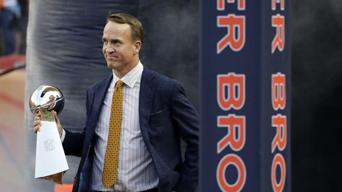 Former Denver Broncos quarterback Peyton Manning carries the Vince Lombardi Trophy from Super...