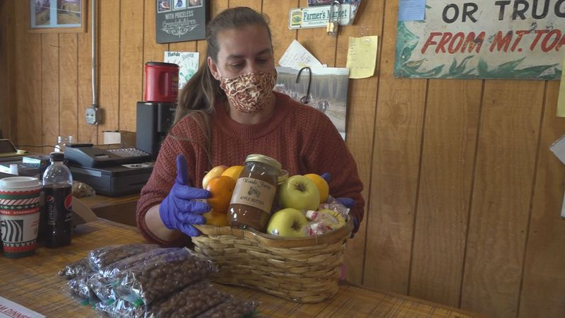 Katherine Adams creates a fruit basket for gift-giving this holiday season at Woods Farms.