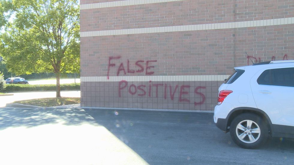 """The words """"false positives"""" and """"power to the people"""" were spray painted on the wall of a..."""