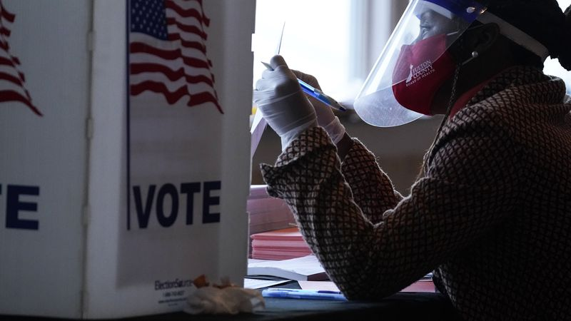 FILE - In this Nov. 3, 2020, file photo, a poll worker talks to a voter before they vote on a...